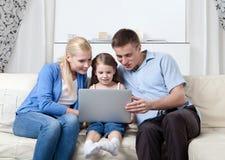 Le famille heureux s'asseyent sur le divan avec l'ordinateur portatif Images stock