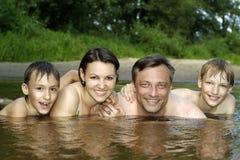 Le famille nage dans le fleuve Photo stock