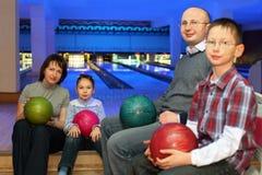 Le famille s'asseyent dans le club et retiennent des billes pour le bowling Image libre de droits