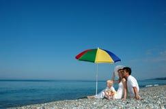 Le famille s'asseyent sur une plage images libres de droits