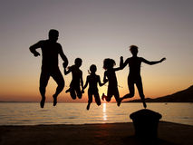 Le famille sautant dans le coucher du soleil de mer Photographie stock
