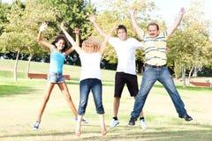 Le famille sautant haut dans le ciel sur un pré vert Photos stock