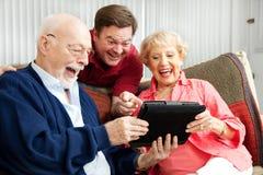Le famille utilise le PC de tablette et rit Photographie stock