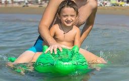 Le farfadern och sonsonen som spelar och plaskar i havsvattnet Stående av den lyckliga pojken för liten unge på stranden av havet royaltyfri bild