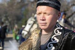 Le faucon se repose sur la main d'un chasseur habillé dans les vêtements kazakhs nationaux - berkutchi image libre de droits