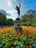 Le faune dansant-Jardin translation The dancing fauna sculptureu in Luxembourg Garden. Beatiful Tulips Paris France.  stock photo