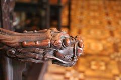 Le fauteuil en bois avec avec le repos de bras a courbé comme tête de dragon Image stock