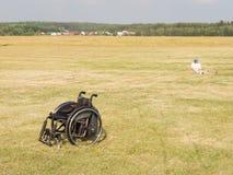 Le fauteuil roulant et la personne s'asseyant sur l'herbe, Moscou REGIO Photos stock