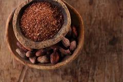Le fave di cacao ed il cioccolato fondente grattato in vecchi cucchiai texured lanciano Fotografia Stock
