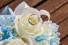 Le fedi nuziali d'argento sono sui petali di artificiale sono aumentato Immagini Stock