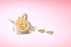 Le fedi nuziali dorate e sono aumentato su fondo bianco Fotografia Stock