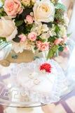Le fedi nuziali si trovano su un bello cuscino in forma di cuore Decorazioni di nozze fotografia stock