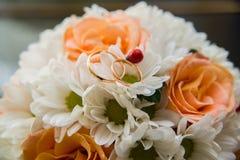Le fedi nuziali si trovano su un mazzo delle rose arancio e dei colori bianchi LadyBug [02] Fotografia Stock Libera da Diritti