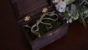 Le fedi nuziali in una scatola di legno hanno riempito di muschio sulla tavola La scatola di legno con le fedi nuziali si trova v Fotografia Stock Libera da Diritti