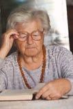 Le femme aîné affiche un livre Photographie stock