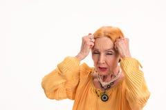 Le femme aîné avec le mal de tête a isolé Photos stock