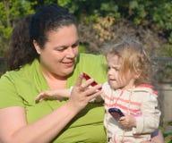 Le femme affiche le téléphone portable à l'enfant en bas âge Photographie stock libre de droits