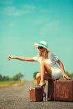 Le femme avec la valise arrête le véhicule Image stock