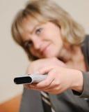 Le femme avec un panneau de commande de télévision photos libres de droits