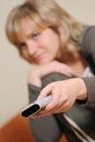 Le femme avec un panneau de commande de télévision Photo stock