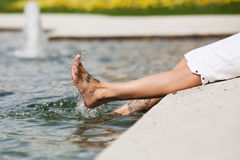 Le femme barbote avec les pieds dans l'eau Photos stock
