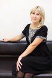 Le femme blond rectifié dans la robe s'assied sur le divan Photographie stock