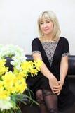 Le femme blond s'assied sur le divan en cuir noir Image stock