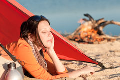 Le femme campant détendent dans la tente par le feu de camp Photographie stock libre de droits