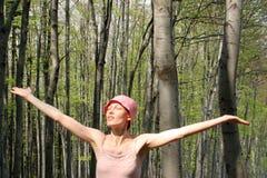 Le femme contacte le soleil dans la forêt photo libre de droits