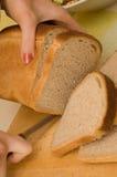 Le femme coupe les parties minces de pain Photo stock