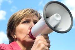 Le femme crie par un mégaphone Photographie stock
