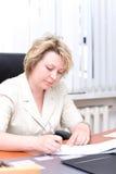 Le femme d'affaires de milieu de la vie écrivent le document Photos stock