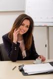 Le femme d'affaires parle du téléphone Photographie stock