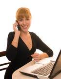 Le femme d'affaires utilise le téléphone et l'ordinateur portatif Photo stock