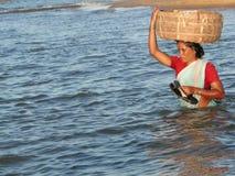 Le femme d'Orissa croise les eaux de marée Image stock