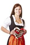 Le femme dans le Dirndl retient le coeur de pain d'épice Photo libre de droits