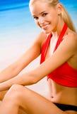 Le femme dans sport-s'usent sur la plage Photo stock