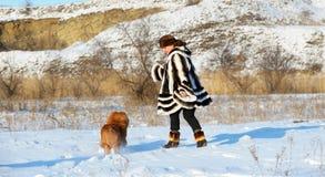 Le femme dans un manteau de fourrure de vison joue avec un crabot Photographie stock libre de droits