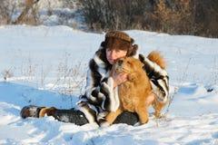 Le femme dans un manteau de fourrure de vison joue avec un crabot Photo stock
