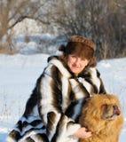 Le femme dans un manteau de fourrure de vison joue avec un crabot Photographie stock