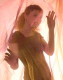 Le femme de beauté derrière un rideau Photos libres de droits