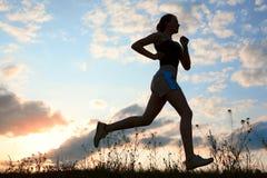 Le femme de silhouette exécutent sous le ciel bleu avec des nuages Image libre de droits