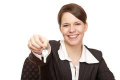 Le femme de sourire livre la clé de maison Photographie stock