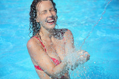 Le femme de sourire se baigne dans le regroupement sous l'eau éclabousse Image libre de droits
