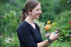 Le femme de sourire travaille dans le jardin Images libres de droits