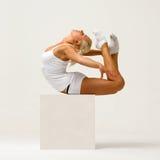 Le femme effectue des exercices gymnastiques Photographie stock
