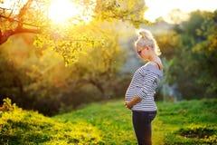 Le femme enceinte reste à côté du coucher du soleil Photographie stock