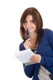 Le femme fait des enregistrements par le crayon lecteur en bloc-notes Photographie stock libre de droits