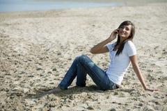 Le femme heureux s'asseyent dans le sable avec un téléphone portable Photographie stock libre de droits
