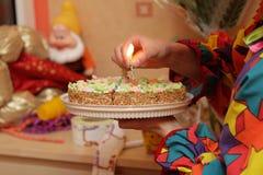 Le femme installe la bougie sur le gâteau image libre de droits